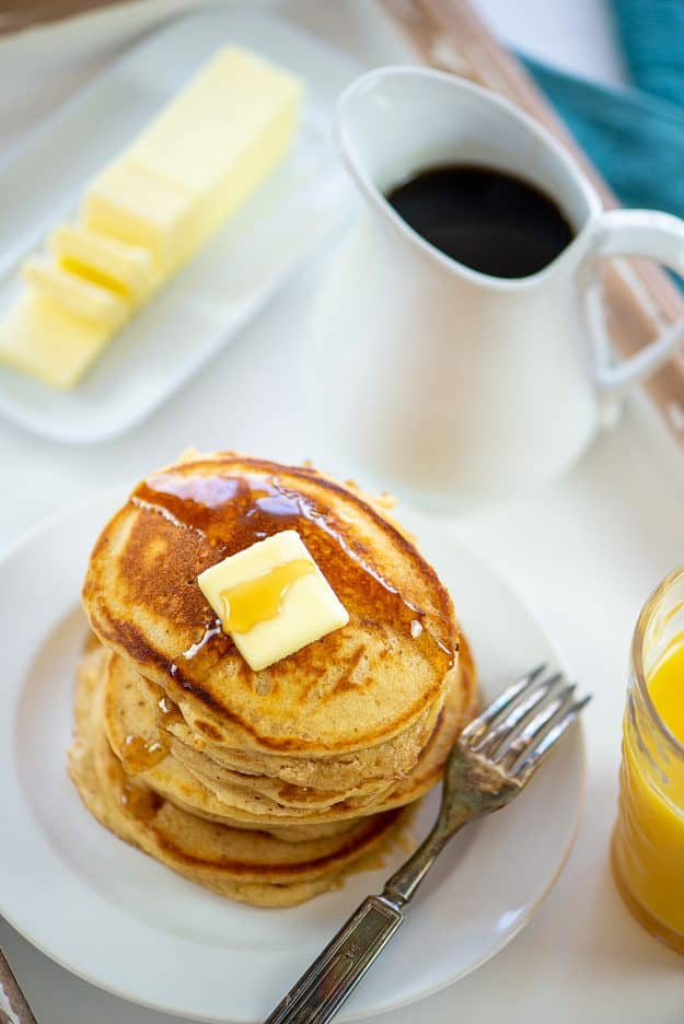 platter with pancakes, orange juice, butter, and syrup.