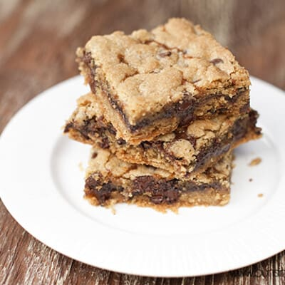 Three cookie bars stacked on a white plate