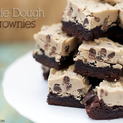 A closeup of stacked cookie dough brownies on a cake stand