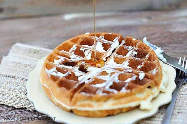 Syrup being poured on a waffle.