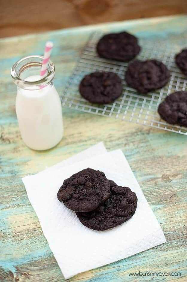 Overhead view of chocolate cookies on a napkin next to a jar of milk