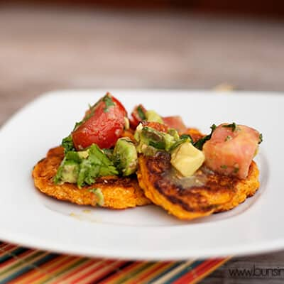 Corn cakes topped with tomato on a white plate