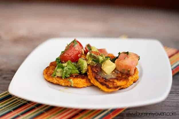 Corn cakes topped with avocado tomato relish on a white plate