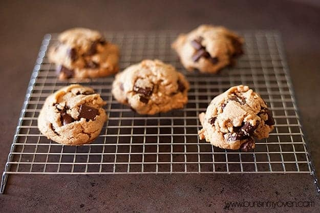 Five peanut butter chocolate chip cookies on a cooling rack