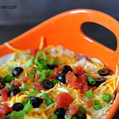 A close up of 7 layer dip in a baking pan