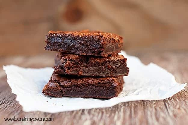 A close up of a side view of stacked up homemade brownies.