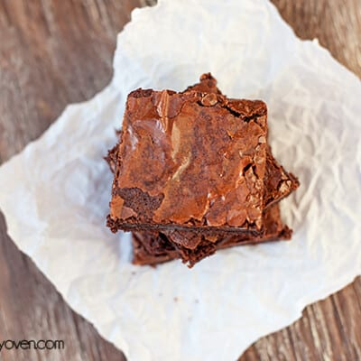 An overhead view of three brownies stacked up on a white napkin.