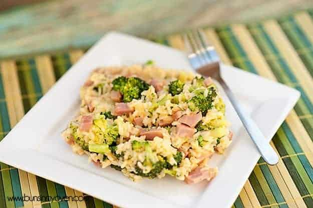 A plate of broccoli and ham on a colorful cloth napkin