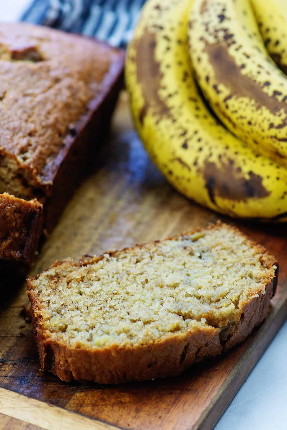 sliced banana bread on wooden cutting board next to ripe bananas