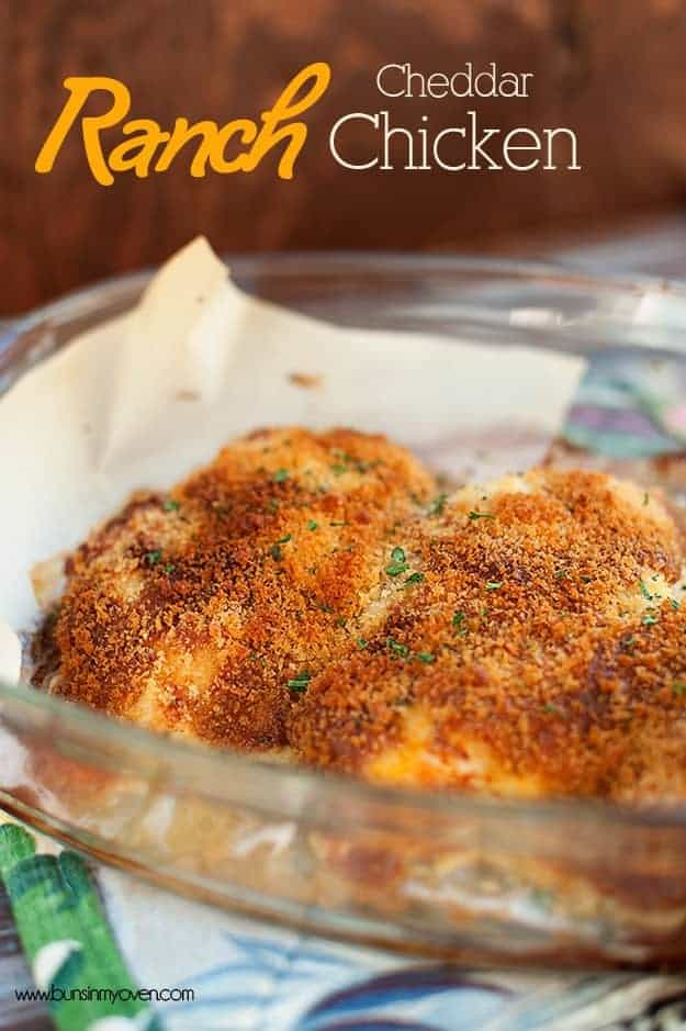 A close up of cheesy crusted chicken breast in a glass baking dish