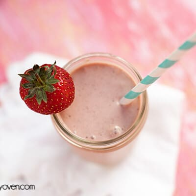 Overhead view of a strawberry milkshake in a glass jar