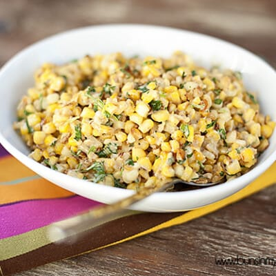 A bowl of Mexican corn on a colorful cloth napkin.