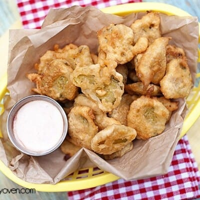 An appetizer basket with fried pickles and ranch dressing in it.