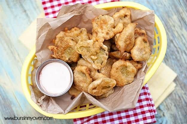 A basket full of fried pickles on top of a checkered cloth napkin