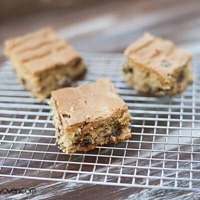Three peanut butter chocolate chip snack cakes on a cooling rack.
