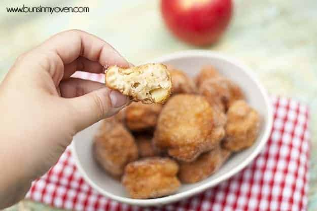 A person holding an apple fritter above a bowl of apple fritters