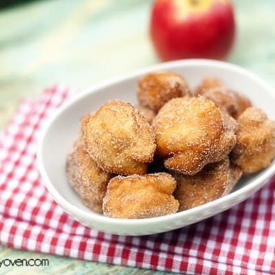 A close up of a bunch of apple fritters in an oval bowl.