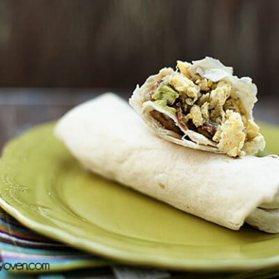 Two breakfast burritos on a green plate.