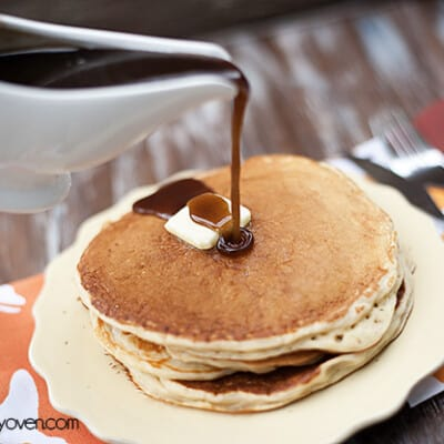 Cinnamon syrup being poured over a stack of pancakes