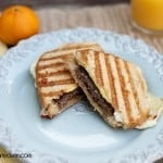 Sausage egg and cheese panini on a decorative plate.