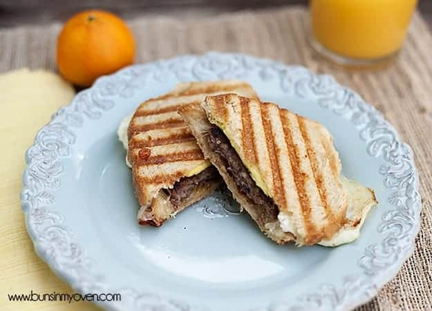 A sausage panini cut into triangle halves with an orange and orange juice in the background.