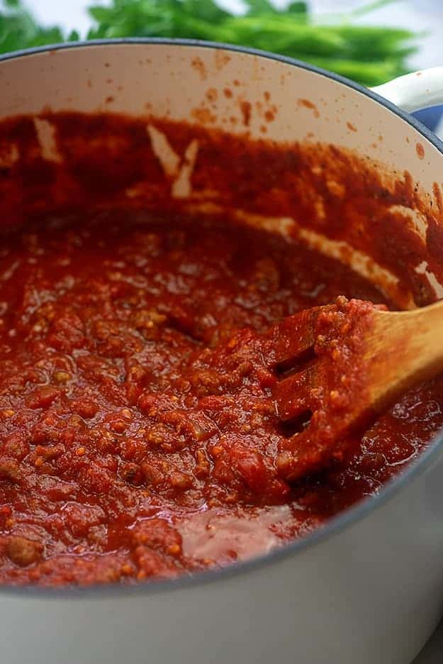Wooden spoon stirring spaghetti sauce in a large white pot.