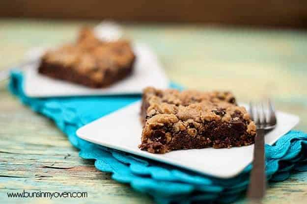 A chocolate chip cookie bar on a white plate on top of a blue cloth napkin.