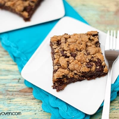A chocolate cookie bar on a square white plate.