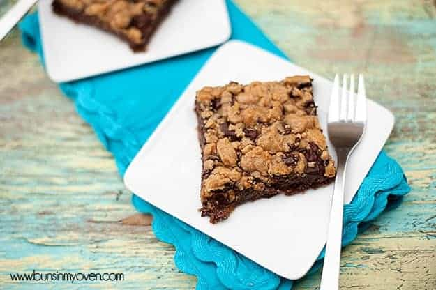 A piece chocolate chip cookie bar and a fork on a white plate.