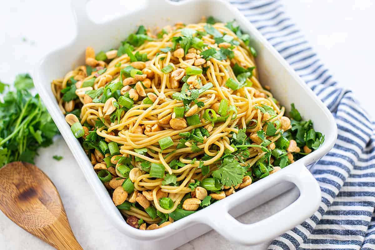 noodles topped with cilantro and peanuts in dish.