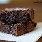 Two brownies stacked on a paper napkin.