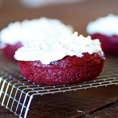 A few red velvet cake donuts on a cooling rack.