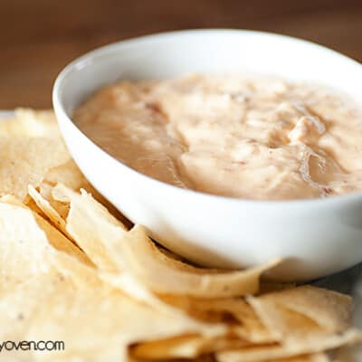 A white bowl of queso dip next to a bunch of tortilla chips on a table.