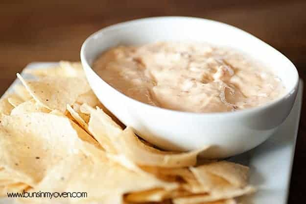 A close up of chips next to a white bowl of queso dip.