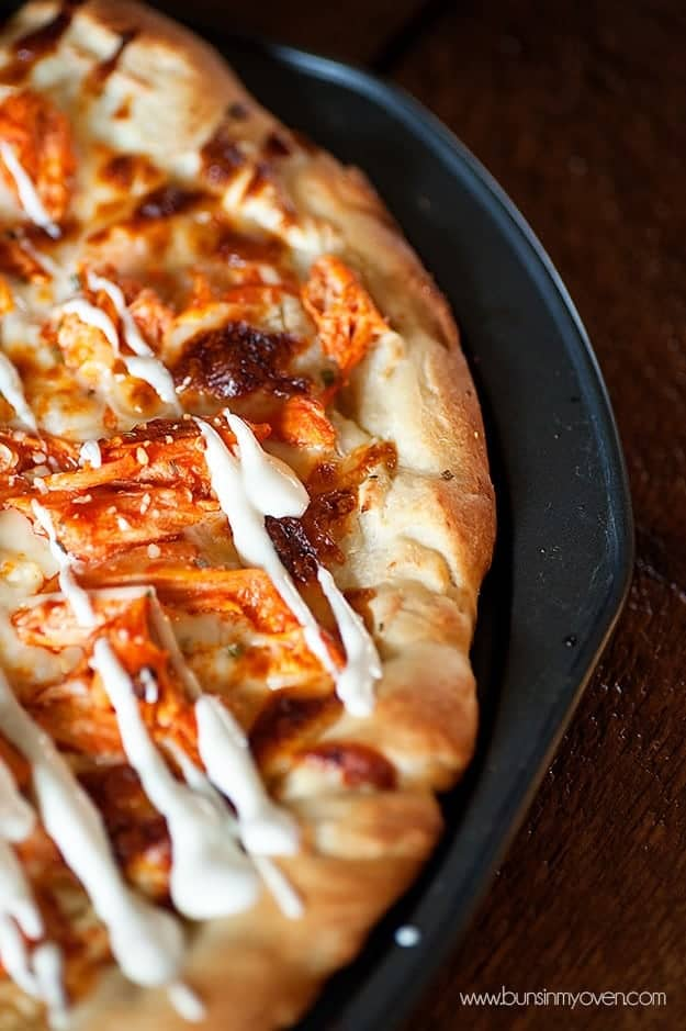 A close up of a pizza topped with ranch dressing