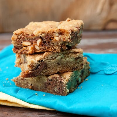 Three stacked up cookies bars on a folded blue napkin