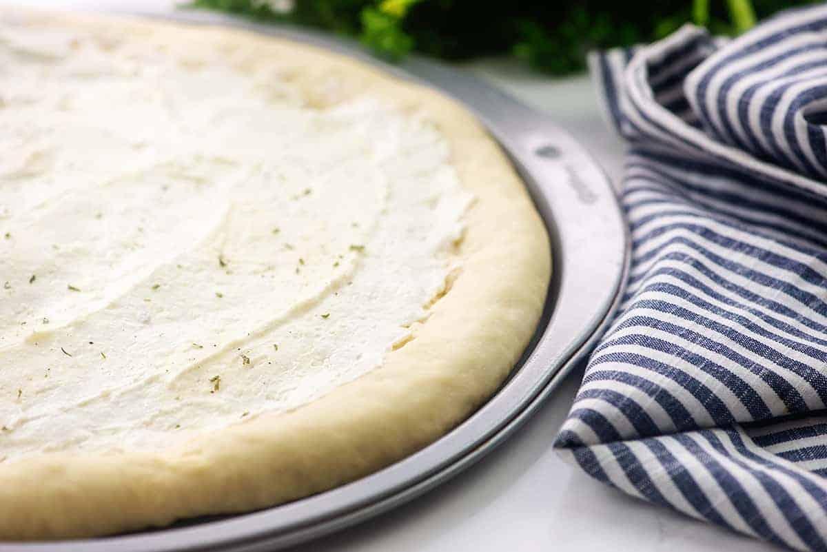 cream cheese mixture on pizza dough.
