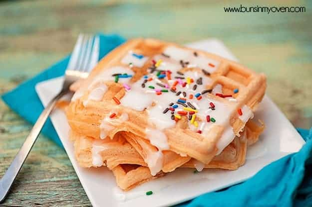 Sprinkled frosting waffles on a small square white plate.