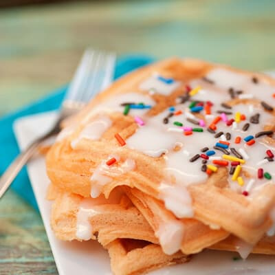 A stack of waffles with icing and sprinkles on top.