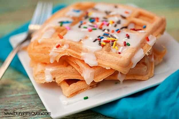 A close up of four waffles topped with colorful sprinkles.