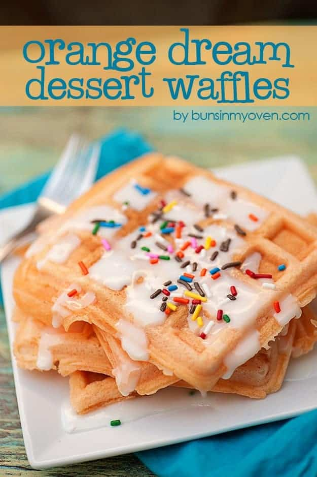 A stack of waffles with white frosting and sprinkles on top.