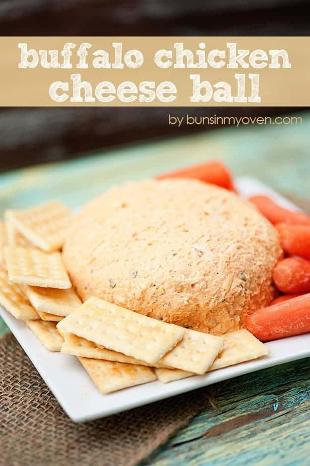 A cheese ball on a square plate surrounded by crackers.
