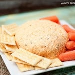 A cheeseball surrounded by crackers and carrots.