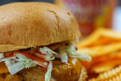 buffalo chicken burger with ranch coleslaw on cutting board by chips