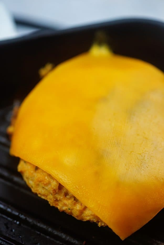 chicken burger with cheddar slice on grill pan