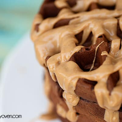 A chocolate waffle topped with peanut butter sauce.