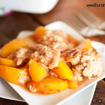 Peach cobbler on a square white plate.