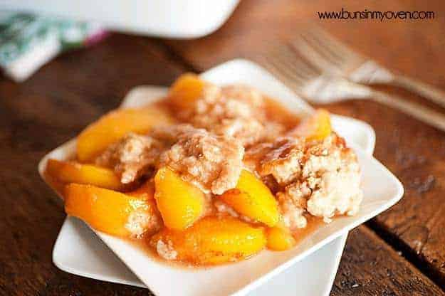 A close up of a plate of peach cobbler.