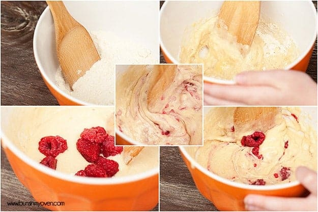 A wooden spoon in a bowl of dough with raspberries in it.