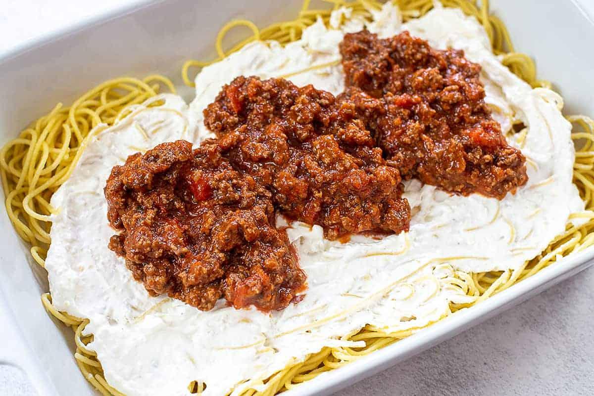 spaghetti, cream cheese, and pasta sauce layered in baking dish.